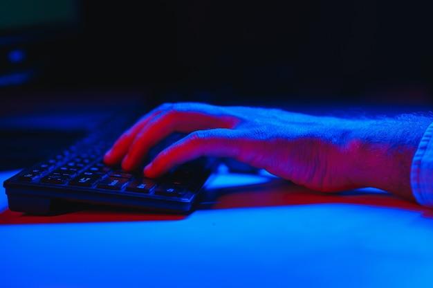Zbliżenie na ręce gracza na klawiaturze, aktywne naciskanie przycisków, granie w gry mmo online. tło jest oświetlone neonami.