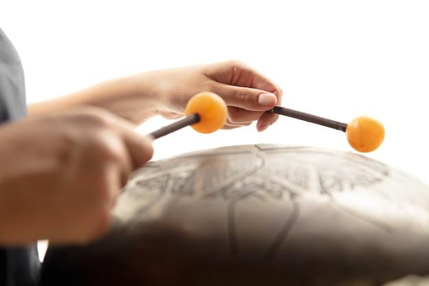 Zbliżenie na ręce grające na bębenku hank na białym tle studio. pojęcie hobby, zawodu, muzyki, tradycji, festiwalu. miejsce na reklamę. instrument etniczny.