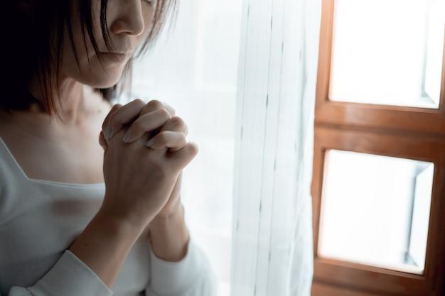 Zbliżenie na ręce kobiety, modląc się w kościele, kobieta wierzyć i modlić się do boga.