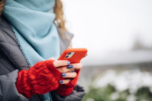 Zbliżenie na ręce kobiety sms-y na smartfonie stojąc na ulicy w zimowym mieście na nowy rok.