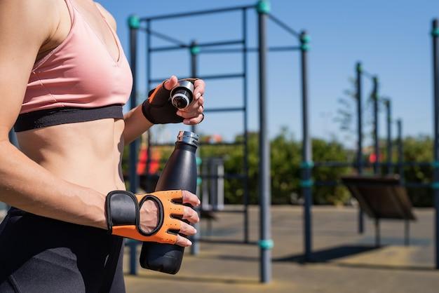 Zbliżenie na ręce kobiety w rękawicach sportowych trzymających butelkę wody na boisku sportowym