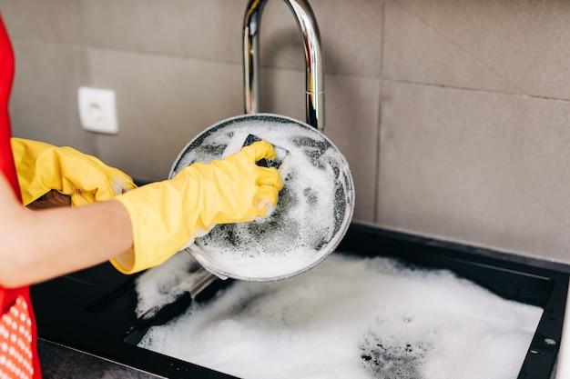 Zbliżenie na ręce kobiety w żółte gumowe rękawice ochronne do mycia naczyń w kuchni.