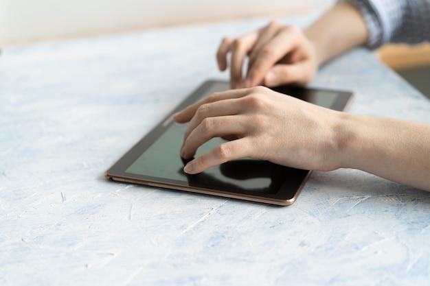 Zbliżenie na ręce kobiety wpisywanie informacji tekstowych na cyfrowym tablecie