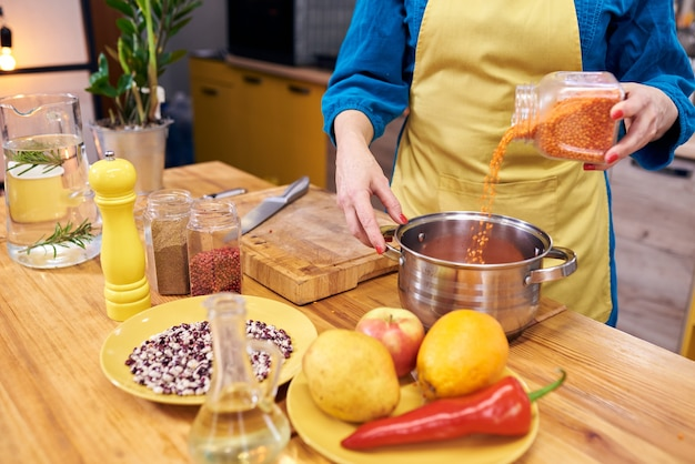 Zbliżenie na ręce kucharza, wlewając czerwoną soczewicę do garnka. zbliżenie