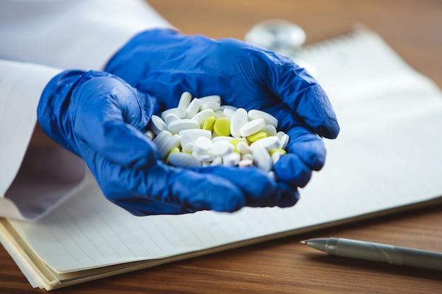 Zbliżenie na ręce lekarzy w niebieskich rękawiczkach ochronnych, dające kilka tabletek na tle drewnianego stołu