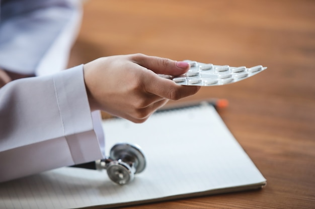 Zbliżenie na ręce lekarzy z arkuszami stetoskopu, dające tabletki pacjentowi na drewnianym tle