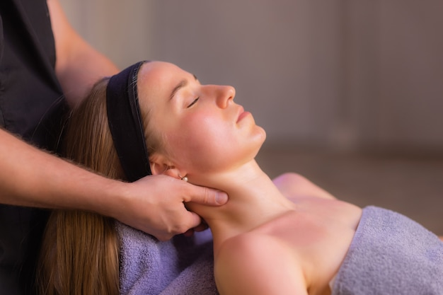 Zbliżenie na ręce masażystki masuje twarz kobiety. kobieta z przyjemnością zamknęła oczy.