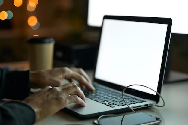 Zbliżenie na ręce mężczyzny siedzącego przy stole przed monitorem komputera i używającego laptopa
