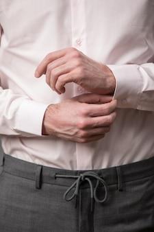 Zbliżenie Na Ręce Mężczyzny W Różowej Bawełnianej Koszuli Z Długim Rękawem I Tekstylnym Paskiem Premium Zdjęcia