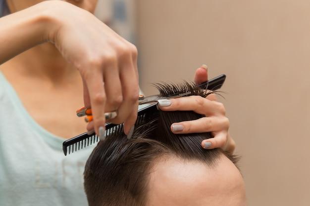 Zbliżenie na ręce młodego fryzjera robiące fryzurę atrakcyjnemu mężczyźnie w salonie fryzjerskim