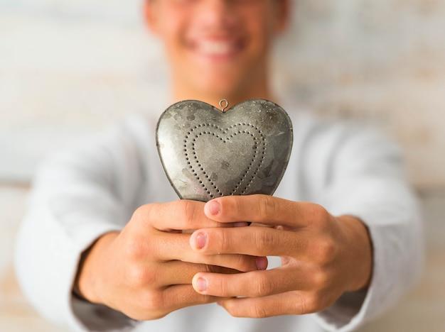 Zbliżenie na ręce nastolatka lub mężczyzny trzymającego w dłoniach metalowe serce uśmiechnięte - miłość i namiętny styl życia