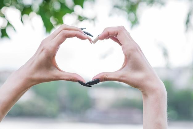 Zbliżenie na ręce pokazujące znak miłości