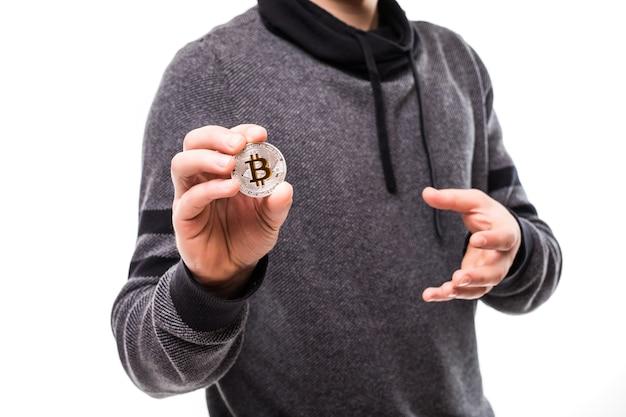 Zbliżenie na ręce przystojny mężczyzna wskazał złote bitcoiny na aparat na białym tle