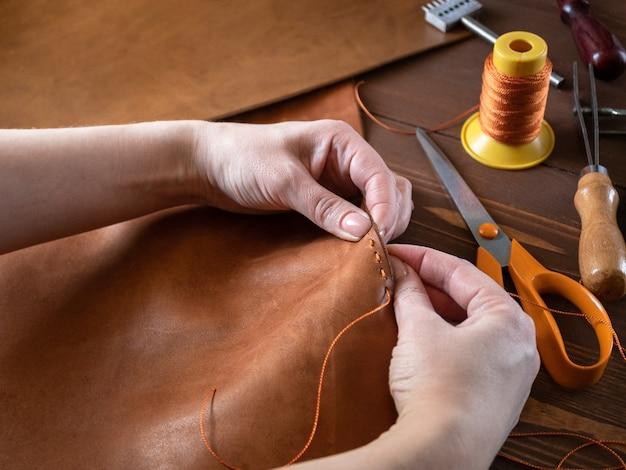 Zbliżenie na ręce rzemieślnicze torebki z prawdziwej skóry