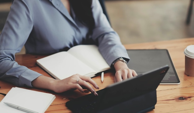 Zbliżenie na ręce studentki porównując notatki na cyfrowym tablecie siedzi na biurku. kobieta za pomocą tabletu w kawiarni