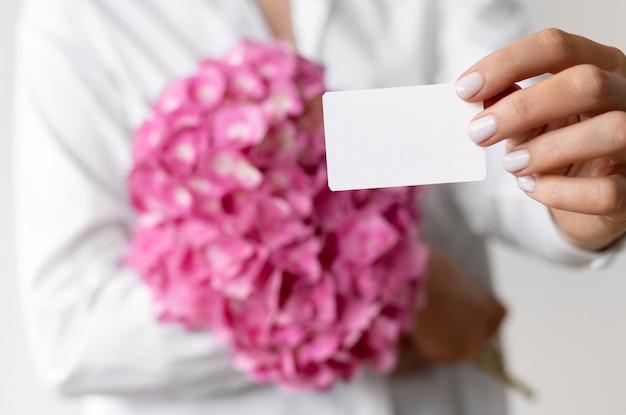 Zbliżenie na ręce trzymające bukiet hortensji i notatkę