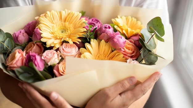 Zbliżenie na ręce trzymające kwiaty urodzinowe