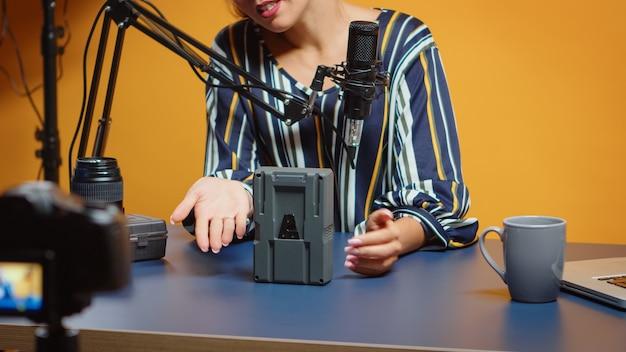 Zbliżenie na recenzenta nowych mediów mówiącego o bateriach v mount w swoim nowym odcinku podcastu. profesjonalna recenzja sprzętu wideo przez twórcę treści, nowego influencera w mediach społecznościowych.