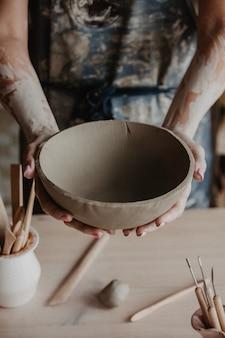 Zbliżenie na rękach młodego mistrza z dużym glinianym talerzem