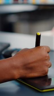 Zbliżenie na rękę afrykańskiego edytora zdjęć rysującego na tablecie graficznym