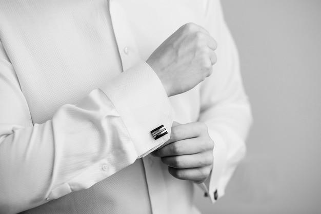 Zbliżenie na rękę człowieka, jak nosi białą koszulę i spinki do mankietów. koncepcja czarno-biała