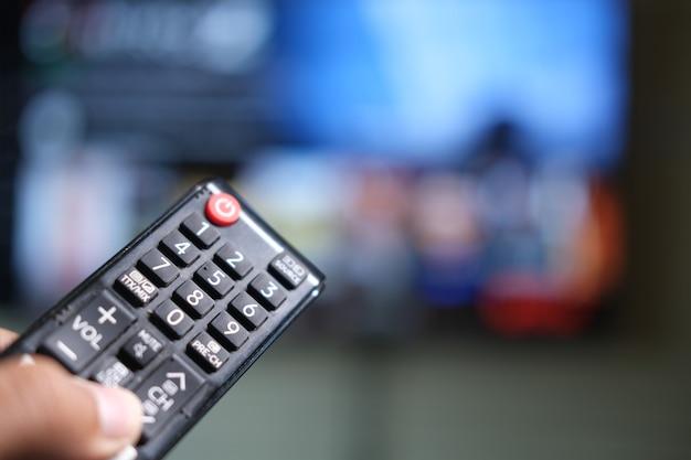 Zbliżenie na rękę mężczyzny trzymającego pilota do telewizora