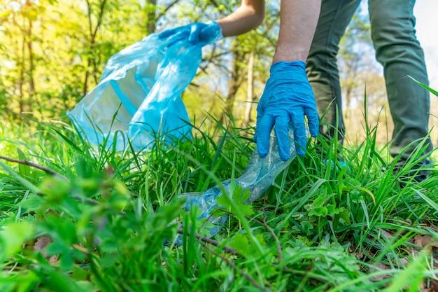 Zbliżenie na rękę mężczyzny w gumowych rękawiczkach zbierających odpady z tworzyw sztucznych w przyrodzie