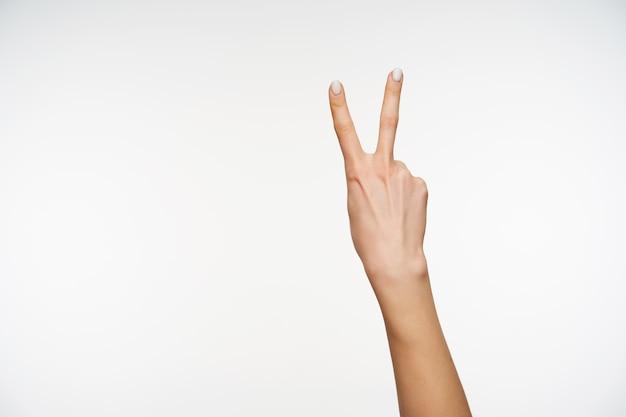 Zbliżenie na rękę młodej zadbanej kobiety podniesionej podczas tworzenia gestu zwycięstwa
