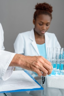 Zbliżenie na rękę podnoszącą próbkę naukową, afrykańskiego technika lub naukowca pracującego z probówkami