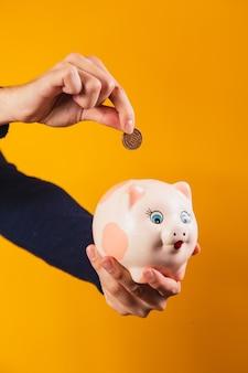 Zbliżenie na rękę wpłacając monetę w skarbonce.