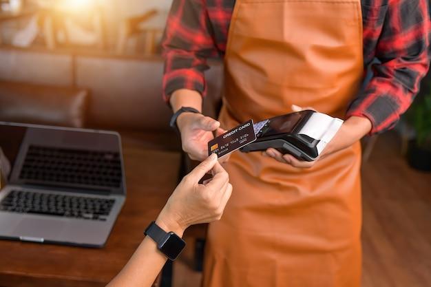 Zbliżenie na rękę za pomocą maszyny do przesuwania kartą kredytową, aby zapłacić, kobieta płaci na przesuwanie karty kredytowej, styl vintage