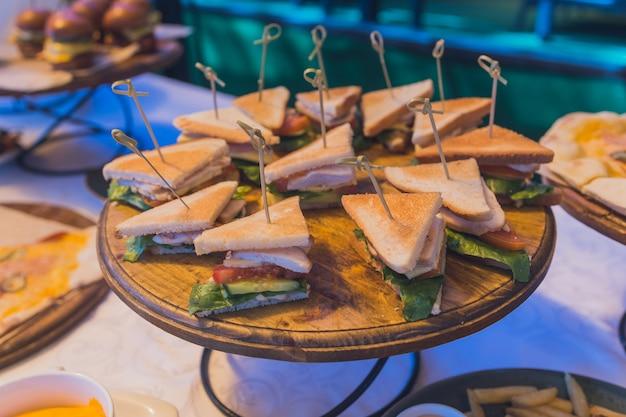 Zbliżenie na różne trójkąty kanapkowe na półmisku cateringowym.