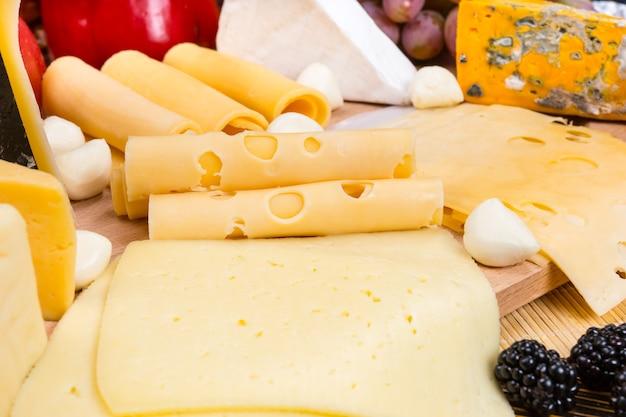 Zbliżenie na różnorodność serów przyozdobionych świeżymi owocami - szczegół przystawki z deski serów dla smakoszy