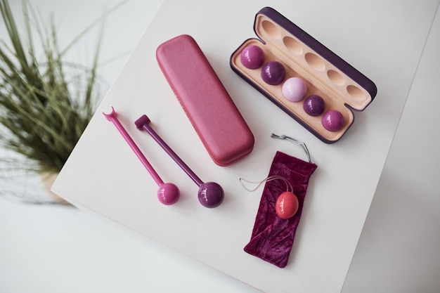 Zbliżenie na różowe kulki dopochwowe i stymulatory leżące na stole. koncepcja imbuildingu i zdrowia kobiety.