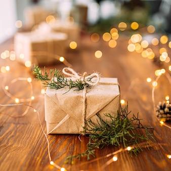 Zbliżenie na rzemiosło zawinięte pudełko na prezent na drewnianym stole z gałęziami girlandy i jodły