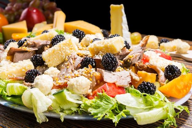 Zbliżenie na sałatkę dla smakoszy ze świeżych warzyw, jeżyn, różnych serów i mięs na rustykalnym drewnianym stole z deską do serów w tle