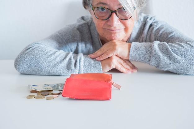 Zbliżenie na seniora liczącego swoje zarobki i ile ma momey - portfel bez pieniędzy na bajkę i dojrzała kobieta patrząca w kamerę