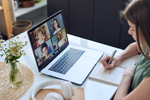Zbliżenie na skoncentrowaną nastolatkę siedzącą przy stole i robienie notatek podczas korzystania z platformy wideokonferencyjnej do edukacji online
