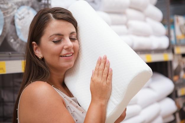 Zbliżenie na śliczną kobietę próbującą ortopedyczną poduszkę w sklepie meblowym, uśmiechając się z zamkniętymi oczami