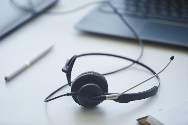 Zbliżenie na słuchawki leżące na stole operatora obsługi klienta w biurze