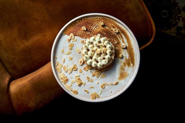 Zbliżenie na smaczne kijowskie ciasto z bezą z orzechami laskowymi, polewą czekoladową i nadzieniem przypominającym masło. ciasto na białym talerzu