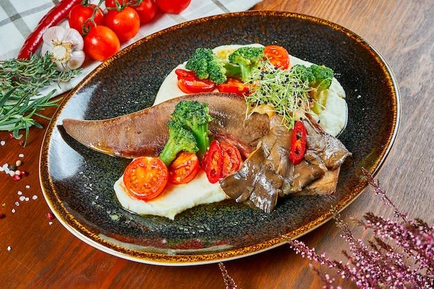 Zbliżenie na smaczny stek z pieczonego języka wołowego ze świeżymi warzywami i puree ziemniaczanym w czarnej płycie na drewnianym stole.