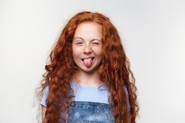 Zbliżenie na śmieszne ładne dziewczynki z rudymi włosami i piegami, pokazuje język w aparacie i mruga, stoi na białym tle.