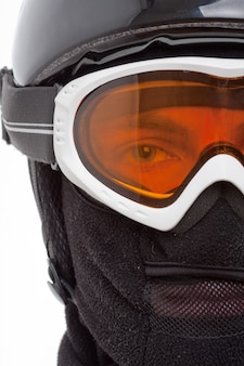 Zbliżenie na snowboardzistę w kominiarce patrzącego przez okulary