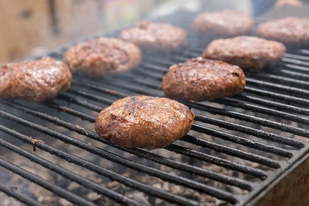 Zbliżenie na soczyste burgery dla smakoszy, gotowanie na grillu wędzarniczym