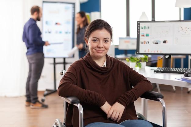 Zbliżenie na sparaliżowaną niepełnosprawną niepełnosprawną kobietę niepełnosprawną koleżankę z pracy patrzącą z przodu uśmiechniętą pracującą w biurze gospodarczym