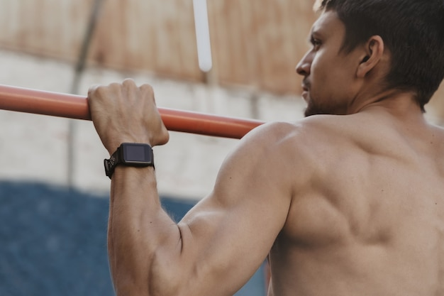 Zbliżenie na sportowca ćwiczącego kalistenikę z smartwatchem na nadgarstku.