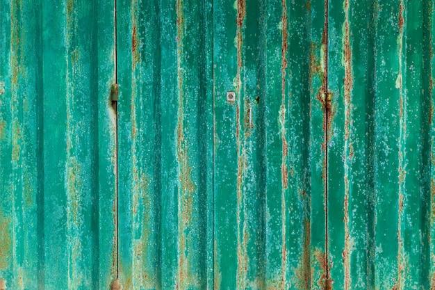 Zbliżenie na starą zardzewiałą płytę, która wisi na ścianie budynku.