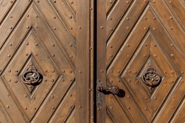 Zbliżenie na starożytne drewniane drzwi z zardzewiałym zamkiem. piękna drewniana tekstura.