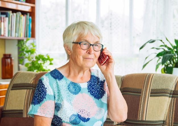 Zbliżenie na starszą kobietę w okularach i siwych włosach, siedząc na kanapie i rozmawiając przez telefon komórkowy.